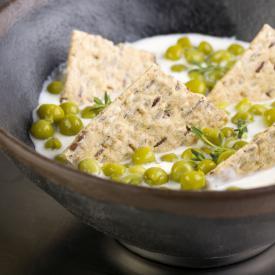 Zuppa di yogurt greco cremoso con piselli finissimi e sfoglie ai semi